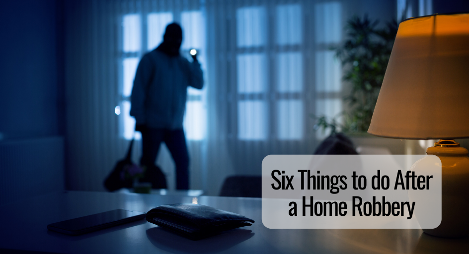 image of burglar entering a person's home, shining a flash light on a phone and wallet on the countertop